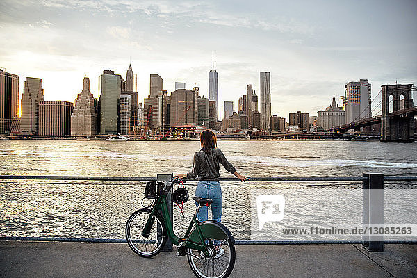 Rückansicht einer Frau mit Fahrrad  die die Stadtansicht betrachtet  während sie auf dem Beobachtungspunkt steht