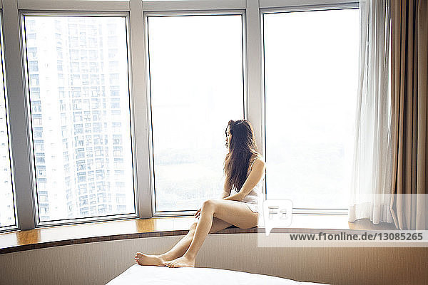Thoughtful female tourist looking through window in hotel room in lingerie