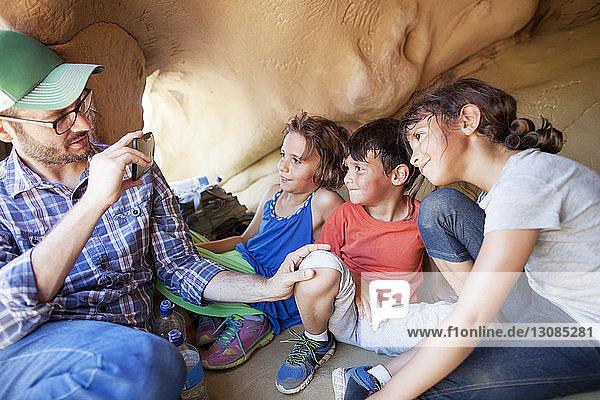 Vater fotografiert Kinder  während er in einer Höhle sitzt
