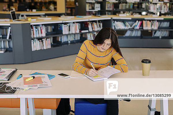 Schrägansicht einer Frau  die am Tisch sitzend in der Bibliothek schreibt