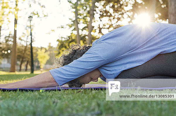 Mature woman doing yoga on grassy field