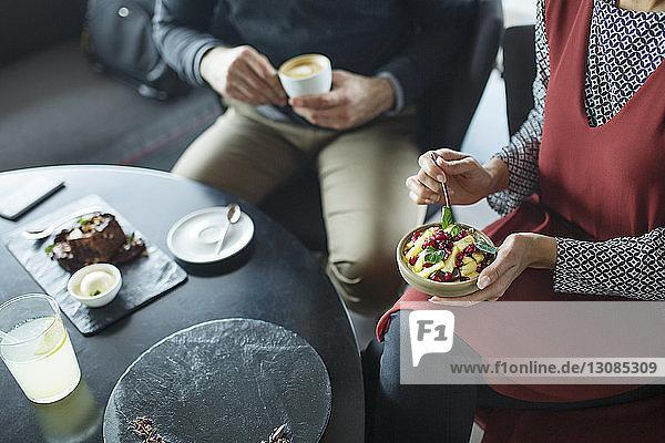 Mittelteil eines Geschäftspaares  das eine Obstschale und Kaffee hält  während es im Café sitzt