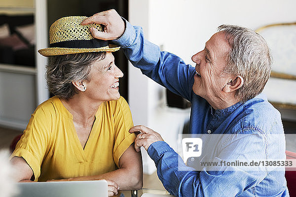 Happy senior man putting sunhat on mature woman while planning vacation at home