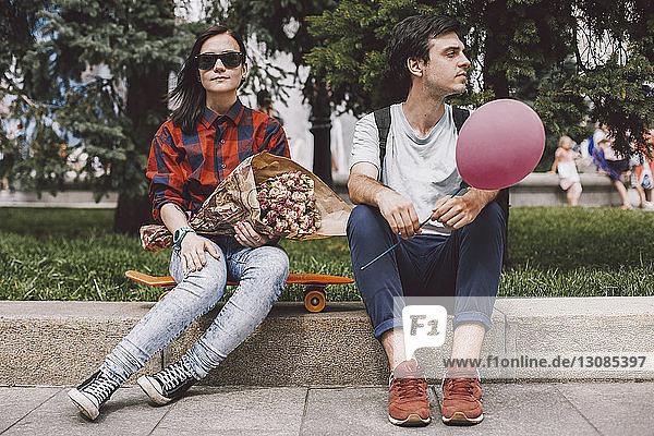 Freundin mit Sonnenbrille hält Blumenstrauss  während sie in der Stadt auf dem Skateboard ihres Freundes sitzt