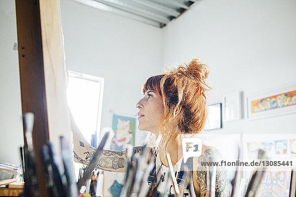 Malerin  die im Atelier stehend eine Skizze auf Leinwand zeichnet