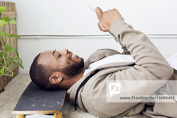 Side view of happy businessman using smart phone while resting head on skateboard at creative office