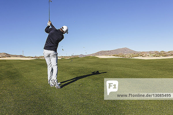 Rear view of golfer playing golf against on field against clear blue sky