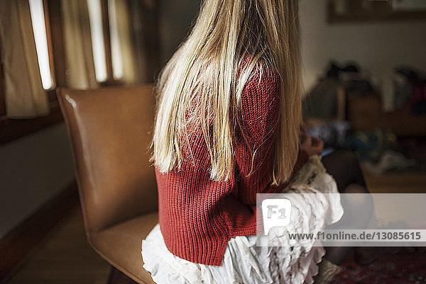 Rückansicht einer Frau  die zu Hause auf einem Stuhl sitzt