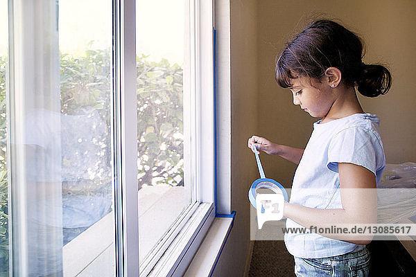 Mädchen hält Klebeband  während sie zu Hause am Fenster steht