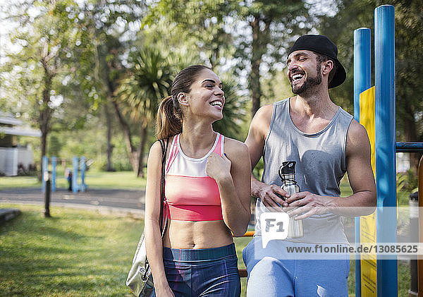 Front view of couple laughing while standing at park