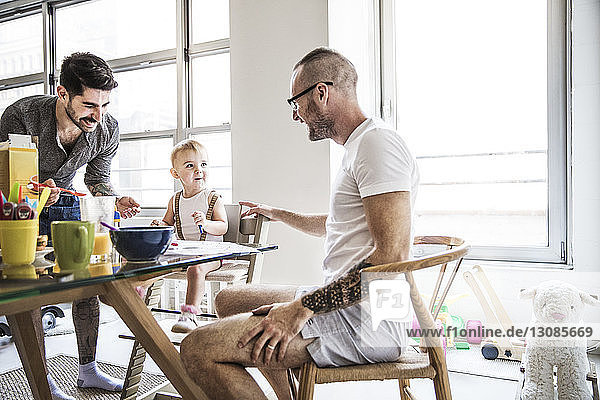 Happy fathers talking while feeding breakfast to daughters at table