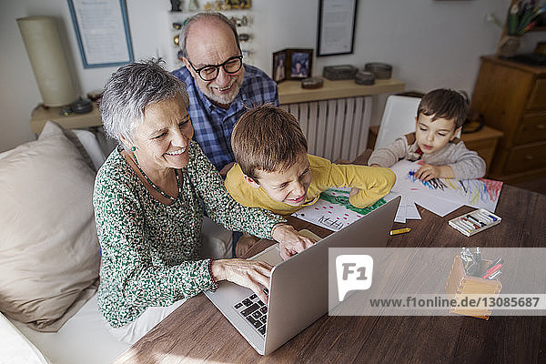 Hochwinkelansicht glücklicher Großeltern und Enkel mit Laptop zu Hause