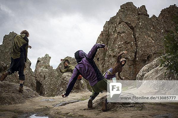 Freunde tanzen bei Hanging rock against sky
