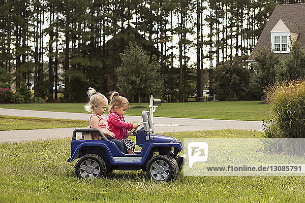 Sisters riding toy car on grassy field in backyard