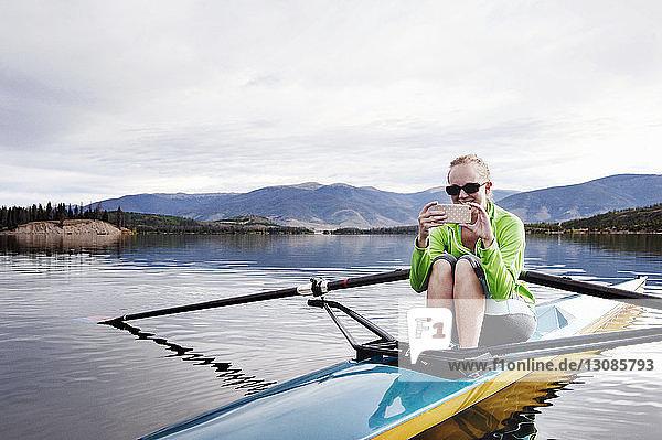 Glückliche Frau telefoniert beim Kajakfahren im See gegen den Himmel