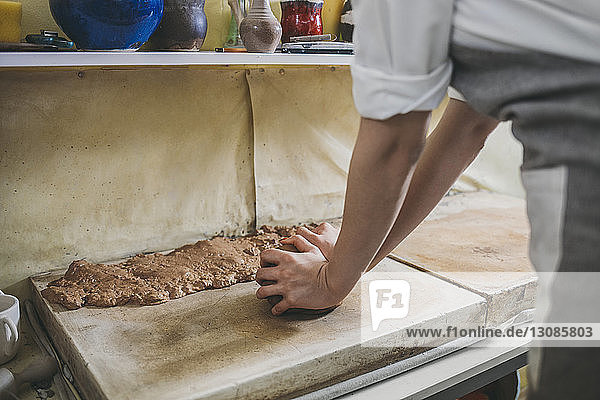 Midsection of female potter kneading clay on table in workshop