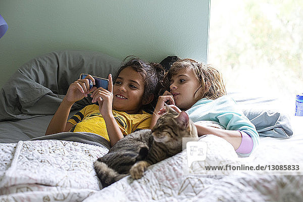 Sisters looking at smart phone while lying with cat on bed