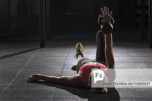 Female athlete lifting kettle bell while lying on floor at gym