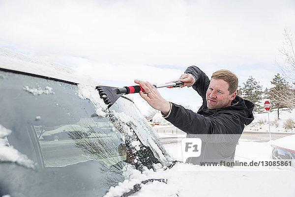 Mann reinigt im Winter Schnee von der Windschutzscheibe eines Autos