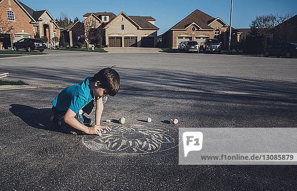 Side view of boy drawing with chalk on asphalt against houses