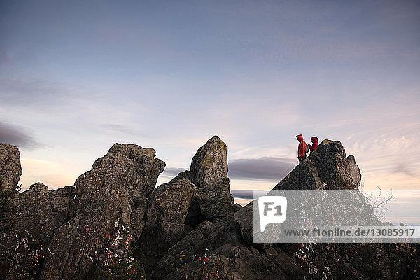 Wanderer stehen auf Berg gegen Himmel