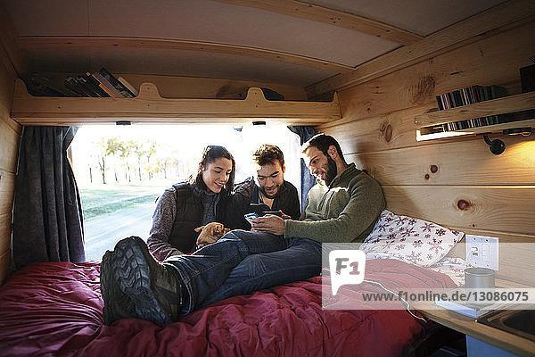 Ehepaar betrachtet Smartphone im Besitz eines Freundes