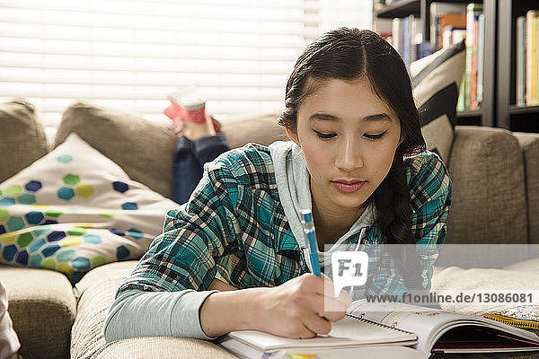 Teenage girl doing homework while lying on couch at home