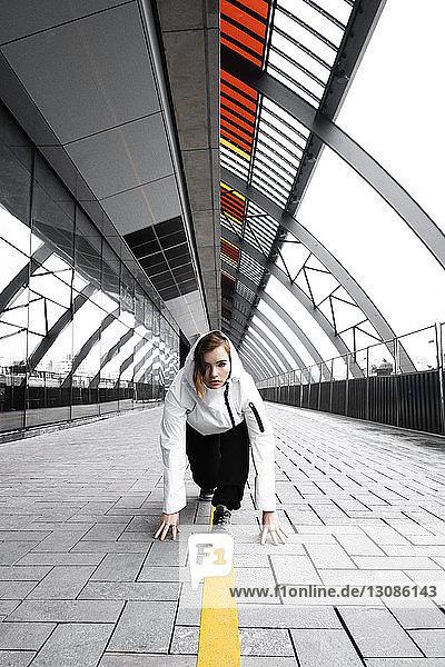 Porträt einer Frau in Startposition auf der Brücke