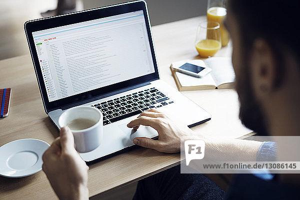 Mann hält Kaffee  während er zu Hause einen Laptop benutzt