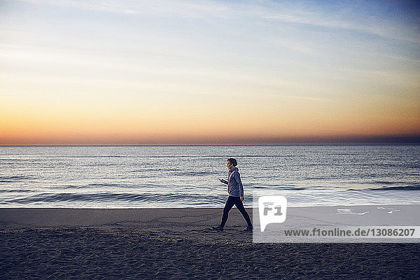 Full length of woman walking at beach against sky