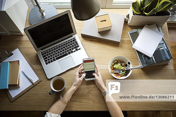 Overhead view of woman using smart phone at desk in home office