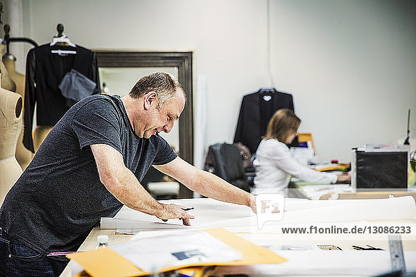 Modedesignerin am Tisch mit einer im Hintergrund sitzenden Mitarbeiterin