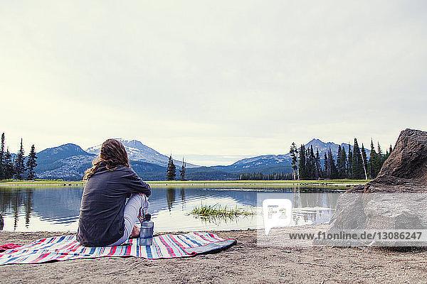 Rückansicht einer am Seeufer sitzenden Frau gegen den Himmel im Shevlin Park