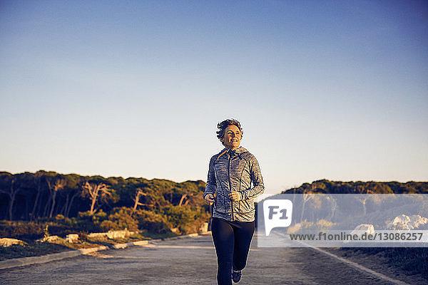 Frontansicht einer Frau  die auf der Straße gegen den klaren Himmel rennt