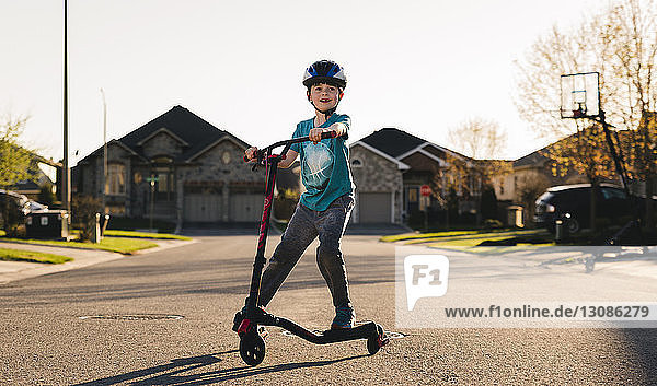 Full length of boy riding push scooter on road