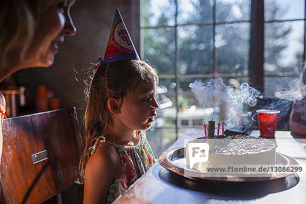 Girl looking at birthday cake with mother at home