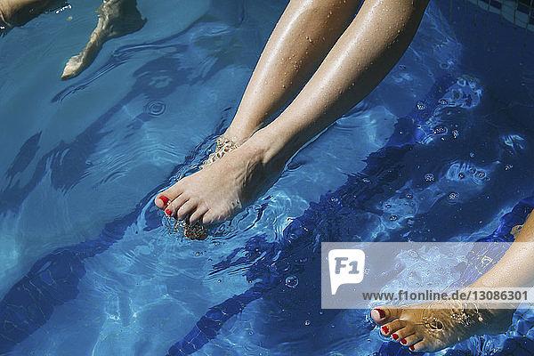 Frauenbeine baumeln im Schwimmbad