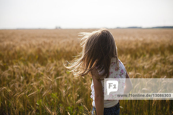 Rear view of girl standing in farm