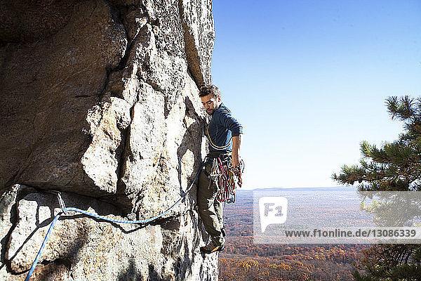 Seitenansicht eines Mannes beim Klettern gegen klaren Himmel