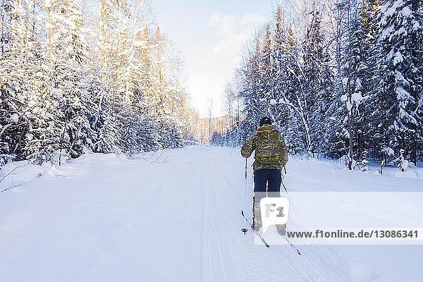 Rückansicht eines Mannes mit Rucksack beim Skifahren auf schneebedecktem Feld