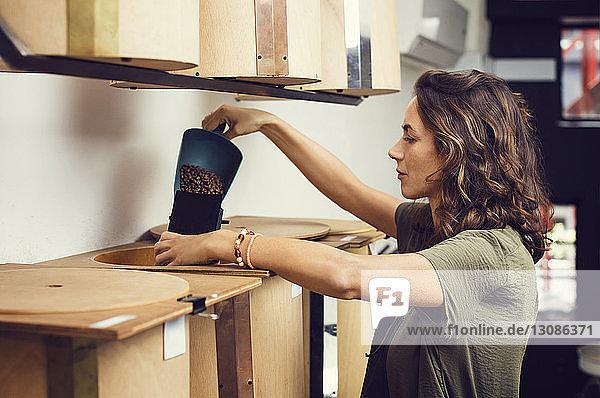 Seitenansicht der Besitzerin  die im Café Kaffeebohnen in Paketen ausschenkt