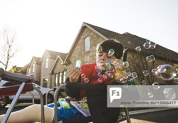 Boy with fractured leg blowing bubbles while sitting on chair against house during sunset