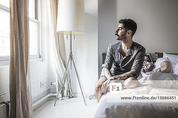 Gay man looking away while partner sleeping on bed