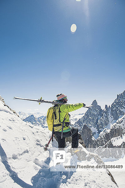 Side view of hiker with skis standing on snow covered mountain against clear blue sky during sunny day