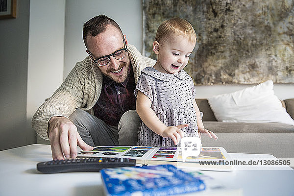 Happy father reading picture book to daughter at home