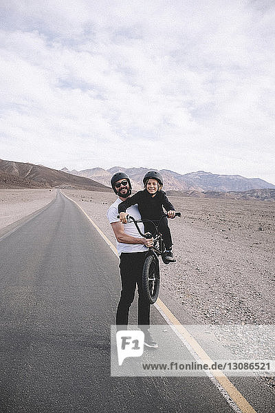 Playful father lifting bicycle with son while standing on country road against mountains and cloudy sky