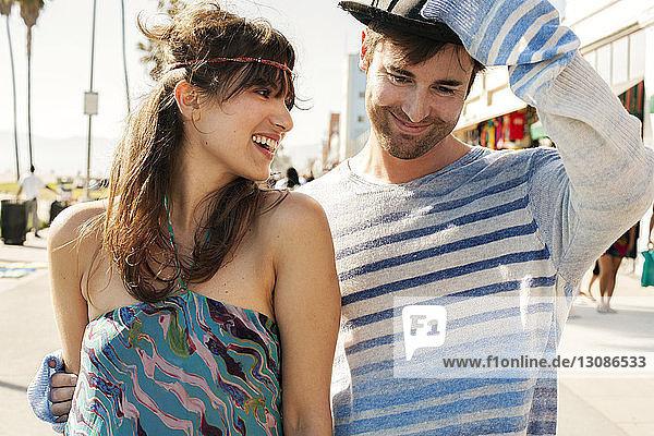 Fröhliche Frau sieht Mann mit Hut auf dem Gehsteig an