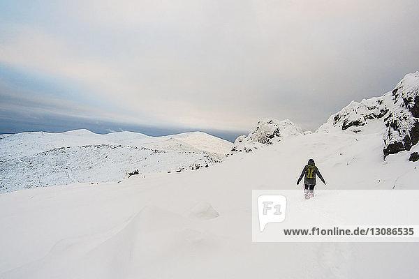 Rückansicht eines Wanderers  der auf einem schneebedeckten Berg vor bewölktem Himmel wandert