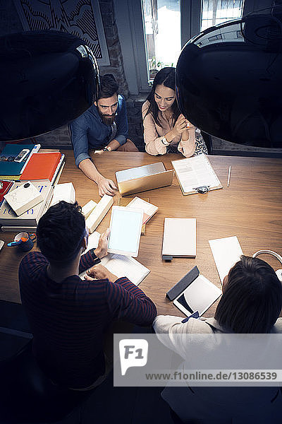 High angle view of colleagues having discussion at conference table in office