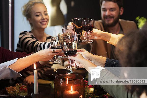 Glückliche Freunde stoßen bei der Weihnachtsfeier auf Wein an